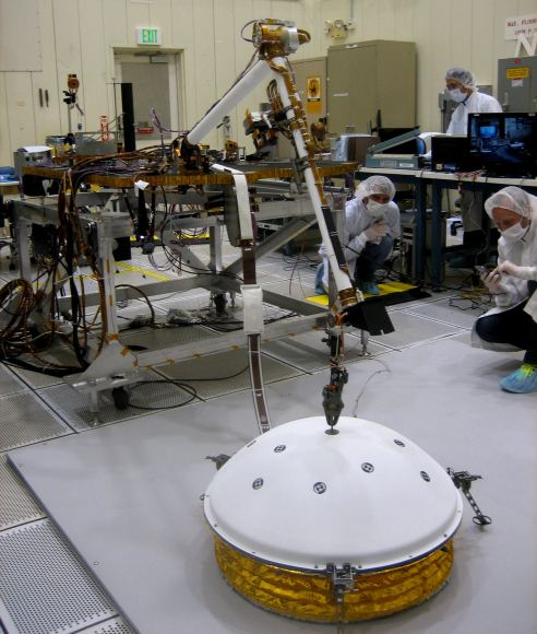 In this image, InSight's Instrument Deployment Arm is practicing placing SEIS on the surface. Image: NASA/Lockheed Martin